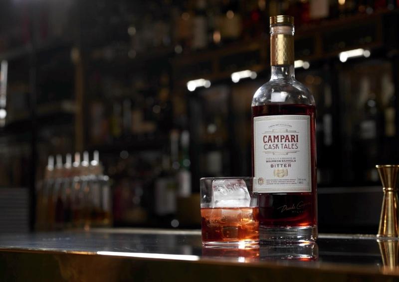 Botella de Campari Task Tales en barra de un bar