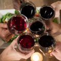Overhead of friends toasting red wine in restaurant
